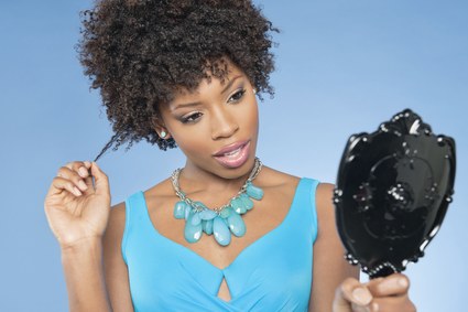 Attractive-African-American-woman-looking-at-herself-in-mirror-pulling-her-curly-hair